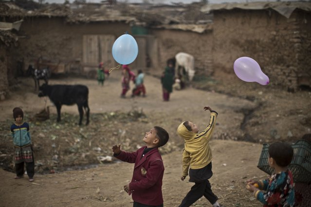 Afghan refugee boys play with balloons near their mud homes on the outskirts of Islamabad, Pakistan, Tuesday, December 30, 2014. (Photo by Muhammed Muheisen/AP Photo)