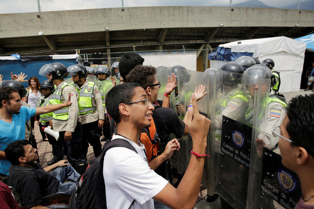 Demonstrators shout slogans in front of riot police during a student rally demanding a referendum to remove Venezuela's President Nicolas Maduro in Caracas, Venezuela October 24, 2016. (Photo by Marco Bello/Reuters)