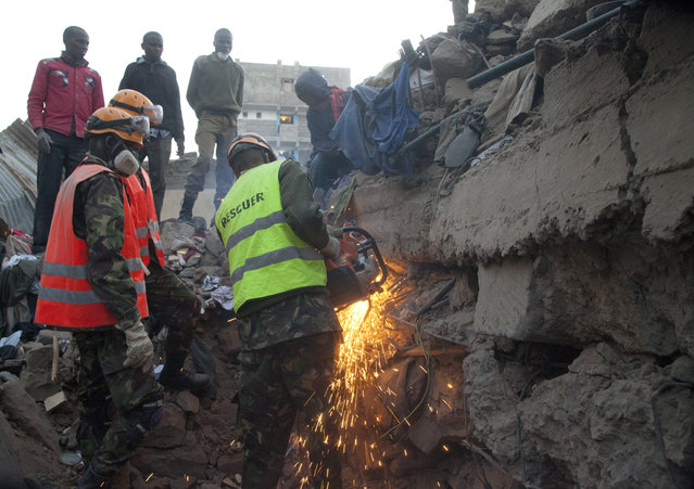 A rescue worker cuts the iron rods on the site of the collapsed building in the capital Nairobi, Kenya, Monday, January 5, 2015. (Photo by Sayyid Azim/AP Photo)