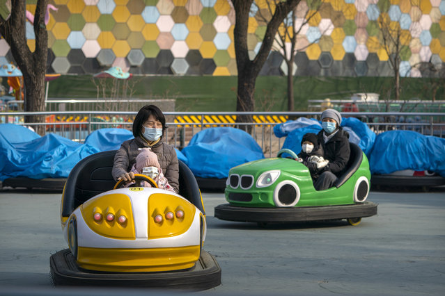 People wearing face masks to protect against the spread of the coronavirus ride on bumper cars at a public park in Beijing, Saturday, January 2, 2021. Wary of another wave of infections, China is urging tens of millions of migrant workers to stay put during next month's Lunar New Year holiday, usually the world's largest annual human migration. (Photo by Mark Schiefelbein/AP Photo)