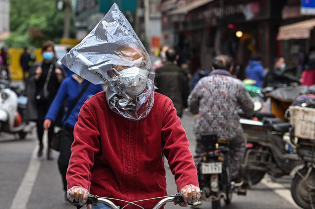 In this file photo taken on April 14, 2020 a man wearing a face mask and a plastic bag on his head rides a bicycle on a street in Wuhan, China's central Hubei province. China has largely brought the coronavirus under control within its borders since the outbreak first emerged in the city of Wuhan late last year. (Photo by Hector Retamal/AFP Photo)