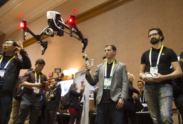 Michael Perry (R) flies a DJI Inspire 1 flying platform during the 2015 International Consumer Electronics Show (CES) in Las Vegas, Nevada January 4, 2015. The remote control quadcopter, with 4K video camera and three-axis gimbal, is a sophisticated filmmaking system straight from the box, said DJI's Randy Braun. The system retails for $2,890.00, he said. (Photo by Steve Marcus/Reuters)
