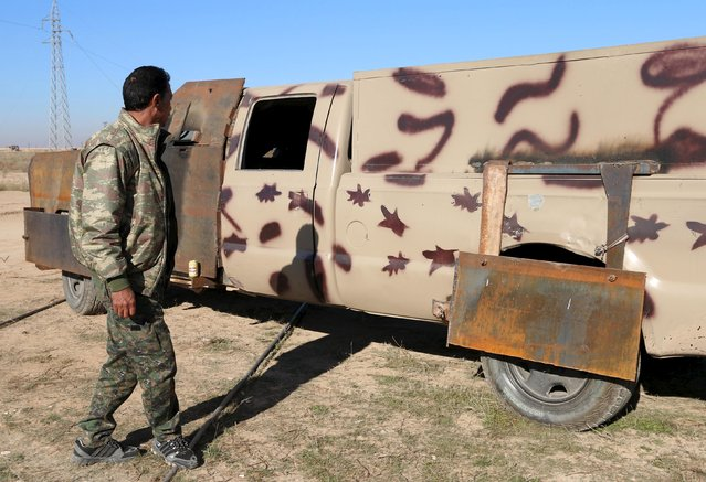A fighter from the Democratic Forces of Syria, stands near a military vehicle which belonged to Islamic State militants, and equipped with explosive materials, in the town of al-Mokhmaliyah, south of Hasaka city, Syria November 24, 2015. (Photo by Rodi Said/Reuters)