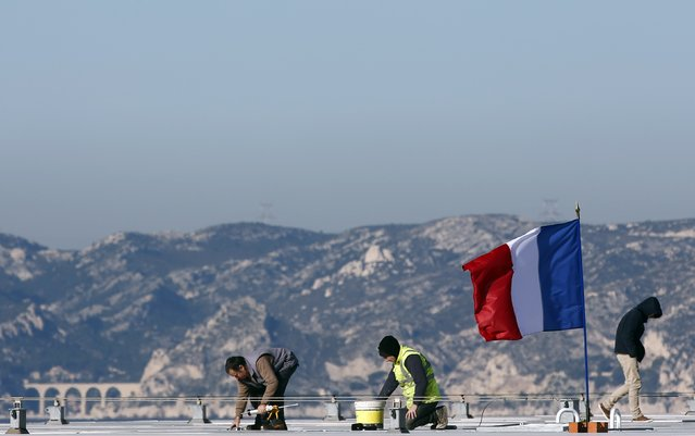 A French national flag flies as workers stand on the roof of the Villa Mediterranee in Marseille, France, November 27, 2015 as the French President called on all French citizens to hang the tricolour national flag from their windows on Friday to pay tribute to the victims of the Paris attacks during a national day of homage. (Photo by Jean-Paul Pelissier/Reuters)
