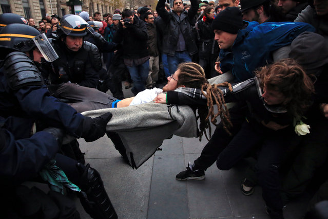 An activist is arrested by riot police officers during a protest ahead of the 2015 Paris Climate Conference at the place de la Republique, in Paris, Sunday, November 29, 2015. (Photo by Thibault Camus/AP Photo)