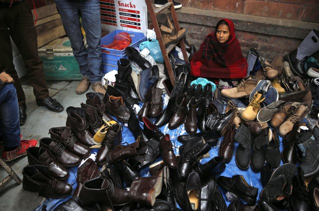 An Indian woman waits for customers at her roadside shoe stall at old quarters of Delhi, India, Sunday, January 11, 2015. Old Delhi despite of being extremely crowded and dilapidated still serves as the symbolic heart of the city. (Photo by Rajesh Kumar Singh/AP Photo)