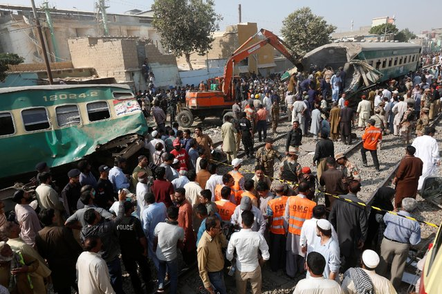 Spectators watch as rescue workers search a train which crashed in Karachi, Pakistan, November 3, 2016. (Photo by Akhtar Soomro/Reuters)