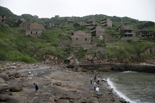 In this May 19, 2018, photo, tourists play at the beach next to abandoned buildings in the former fishing village of Houtouwan on the remote island of Shengshan, 90 kilometers off the coast of Shanghai. (Photo by Sam McNeil/AP Photo)