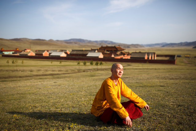 Senior Buddhist monk Lobsang Tayang sits outside the Amarbayasgalant Monastery in the Baruunburen district, Selenge province, Mongolia, April 26, 2018. (Photo by Thomas Peter/Reuters)