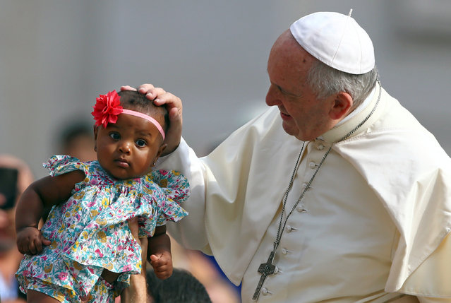 Pope Francis blesses a child as he arrives to lead the Wednesday general audience in Saint Peter's square at the Vatican, June 13, 2018. (Photo by Tony Gentile/Reuters)
