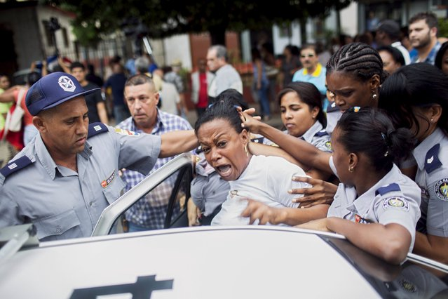 Cuban security personnel detain a member of the Ladies in White dissident group during a protest on International Human Rights Day, Havana, December 10, 2015. (Photo by Alexandre Meneghini/Reuters)