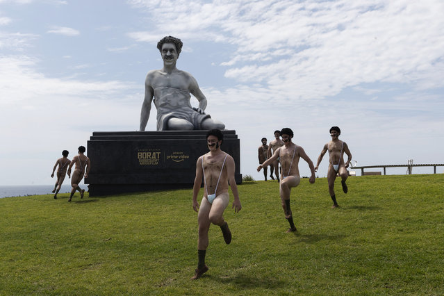 "A group of people dressed in ""Maskini's"" dance around a a six meter high statue of the movie character Borat in Marks Park in Bondi during a press call for the Borat Subsequent Moviefilm on October 22, 2020 in Sydney, Australia. The statue arrived via helicopter, traveling over Sydney's iconic Bondi Beach for the event. (Photo by Brook Mitchell/Getty Images)"
