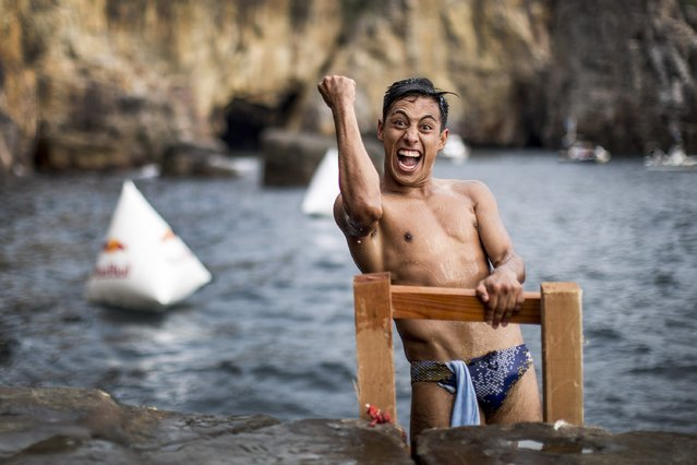 In this handout image provided by Red Bull, Sergio Guzman of Mexico celebrates while climbing out of the water after his winning dive from the 28 metre platform during the eighth stop of the Red Bull Cliff Diving World Series, Shirahama, Japan. (Photo by Dean Treml/Red Bull via Getty Images)