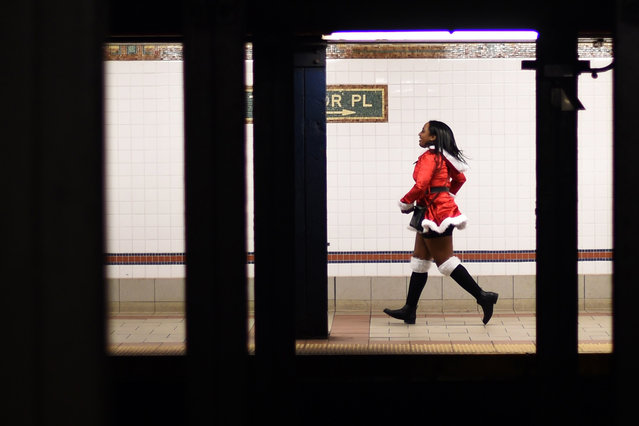 A woman dressed in a Santa outfit runs for the subway during the SantaCon in New York City on December 12, 2015. SantaCon is an event where groups of men and woman dress as Santa. (Photo by Timothy A. Clary/AFP Photo)