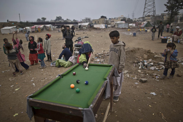 Pakistani boys plays snooker for 10 Rupees (U.S. 10 cents) per game, in a slum in Rawalpindi, Pakistan, Friday, January 23, 2015. (Photo by Muhammed Muheisen/AP Photo)
