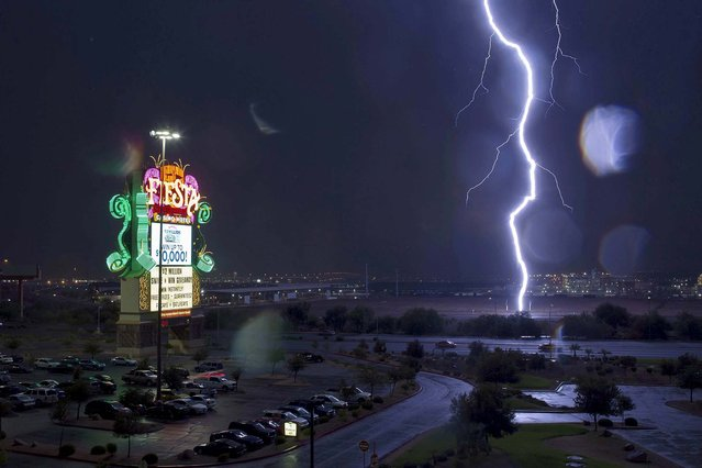 Lightning strikes a fence near the Fiesta hotel-casino in Henderson, Nevada as a thunderstorm makes its way through the Las Vegas Valley, on July 19, 2013. (Photo by Steve Marcus/Las Vegas Sun)