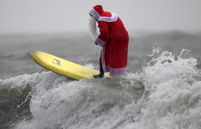 A member of the Langland Board Surfers group takes part in a Surfing Santa competition at Langland Bay in Gower, Wales, December 19, 2015. (Photo by Rebecca Naden/Reuters)