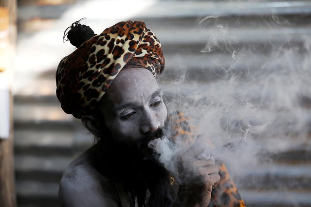"""A Sadhu or Hindu holy man smokes inside his tent ahead of the first Shahi Snan at """"Kumbh Mela"""" or the Pitcher Festival, in Haridwar, India, March 10, 2021. (Photo by Anushree Fadnavis/Reuters)"""