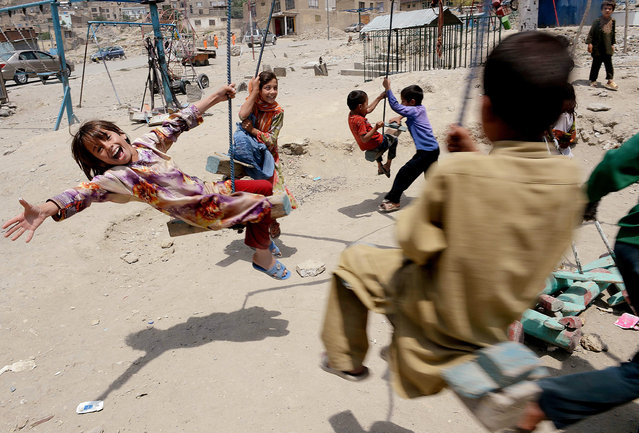 Afghan children play on a swing near a cemetery in Kabul on July 31, 2013. Civilian casualties in the Afghan war rose 23 percent in the first half of this year due to Taliban attacks and increased fighting between insurgents and government forces, the UN said on July 30. (Photo by Shah Marai/AFP Photo)