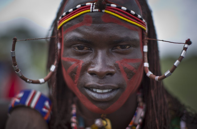 A Maasai warrior wears his hair in the traditional style, at the annual Maasai Olympics in the Sidai Oleng Wildlife Sanctuary near to Mt Kilimanjaro, in southern Kenya Saturday, December 13, 2014. (Photo by Ben Curtis/AP Photo)
