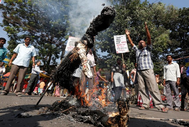 People shout slogans as they burn an effigy of the Indian Prime Minister Narendra Modi during a protest against the government's decision to withdraw 500 and 1000 Indian rupee banknotes from circulation, according to a media release, in Siliguri, India, November 16, 2016. (Photo by Rupak De Chowdhuri/Reuters)