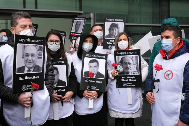 Healthcare workers hold carnations and pictures of their colleagues who have passed away due to the coronavirus disease (COVID-19) outbreak, during a demonstration to mark the first anniversary of the first coronavirus diagnosis in Turkey, in front of the Prof. Dr. Cemil Tascioglu City Hospital in Istanbul, Turkey on March 11, 2021. (Photo by Murad Sezer/Reuters)