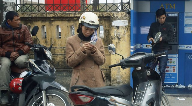 A woman (C) types on a mobile phone along a street in Hanoi February 2, 2015. Vietnam is ringing in changes next month to make way for a standardized phone numbering plan, but is struggling to get through to businesses hung up on how much it will cost them. (Photo by Reuters/Kham)