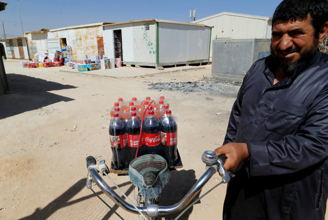 A Syrian man transports bottles of soft drinks, to be distributed to customers, with his bicycle in Zaatari refugee camp near the border with Syria, in Mafraq, Jordan October 15, 2016. (Photo by Ammar Awad/Reuters)
