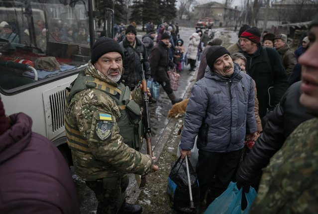 A member of the Ukrainian armed forces assists local residents onto a bus, to flee the military conflict, in Debaltseve, eastern Ukraine, February 6, 2015. (Photo by Gleb Garanich/Reuters)