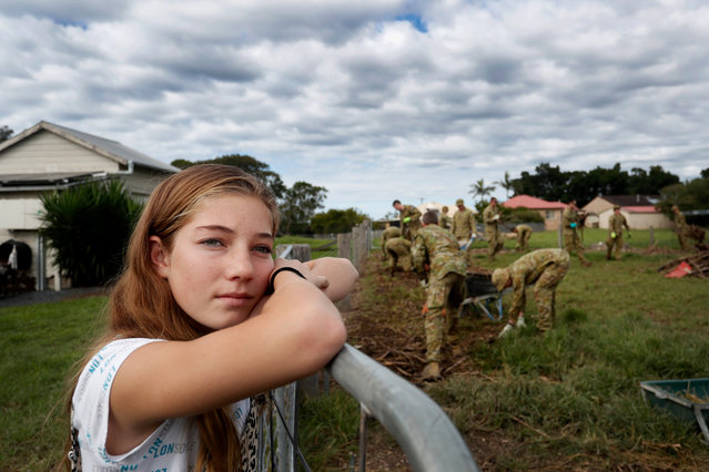 Mia Harris looks on as Australian Defence emergency support team members help clear flood damaged land at her family home in the small township of Croki on March 29, 2021 in Taree, Australia. (Photo by Lisa Maree Williams/Getty Images)
