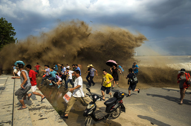Visitors run away as waves from a tidal bore surge past a barrier on the banks of Qiantang River, in Hangzhou Zhejiang province, on August 24, 2013. (Photo by Reuters/Stringer via The Atlantic)