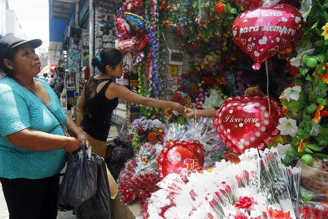 People buy heart-shaped balloons and artificial flowers from a stand ahead of Valentine's Day outside the Central Market in downtown Lima February 12, 2015. (Photo by Enrique Castro-Mendivil/Reuters)