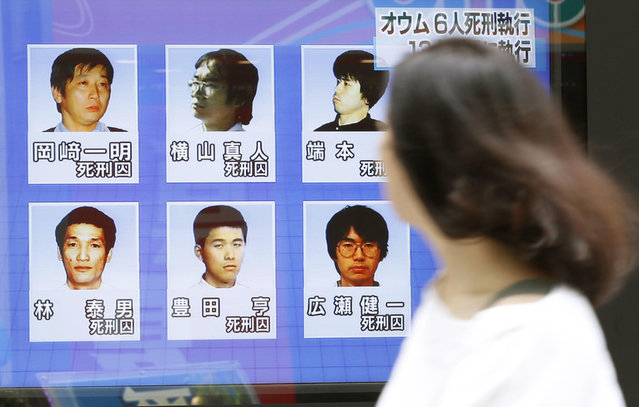 A woman walks on a street while watching TV news reporting executions of six members of Aum Shinrikyo, in Tokyo Thursday, July 26, 2018. Japan executed on Thursday all the six members of the doomsday cult who remained on death row for a series of crimes in the 1990s including a sarin gas attack on Tokyo subways that killed 13 people. Images on the screen are, from top left clockwise, Kazuaki Okasaki, Masato Yokoyama, Satoru Hashimoto, Kenichi Hirose, Toru Toyoda and Yasuo Hayashi. (Photo by Shinji Kita/Kyodo News via AP Photo)