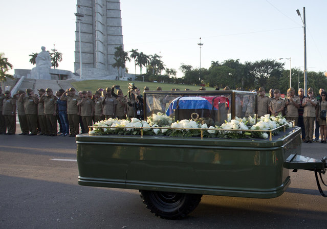 Military officers salute as, placed in a small coffin covered by a Cuban flag, the ashes of Cuban leader Fidel Castro are driven by the monument to Indepence hero Jose Marti, left, along Revolution Square in Havana, Cuba, Wednesday November 30, 2016. Castro's ashes have begun a four-day journey across Cuba from Havana to their final resting place in the eastern city of Santiago. (Photo by Desmond Boylan/AP Photo)