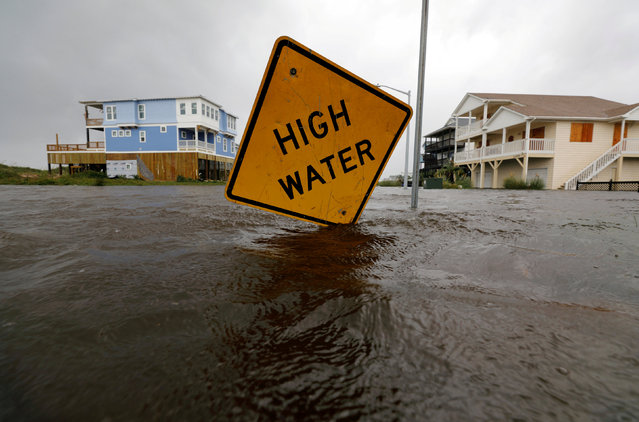 Flood waters lap at a high water warning sign that was partially pushed over by Hurricane Florence on Oak Island, North Carolina, U.S., September 15, 2018. (Photo by Jonathan Drake/Reuters)