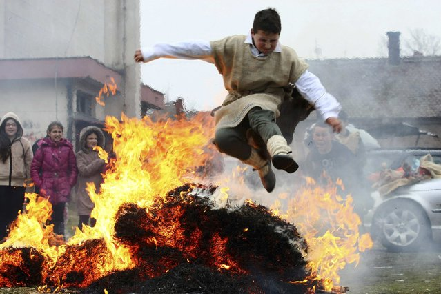 A boy jumps over a fire during Bele Poklade carnival celebrations in the village of Lozovik, some 100 km (62 miles) from the capital Belgrade, February 22, 2015. (Photo by Djordje Kojadinovic/Reuters)