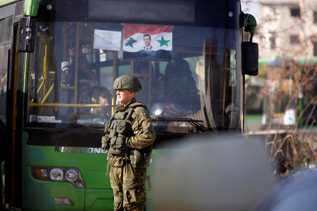 A Russian soldier stands near a bus carrying people who came back to inspect their homes in government controlled Hanono housing district in Aleppo, Syria December 4, 2016. (Photo by Omar Sanadiki/Reuters)