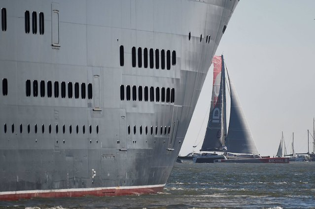 """British cruise ship Queen Mary 2  and Ultim trimarans take the start of """"The Bridge 2017"""" transatlantic race on June 25, 2017 from the French western port city of Saint-Nazaire. """"The Bridge 2017"""" is a 3,152-mile (5,837 km) race between the British cruise liner RMS Queen Mary 2 and four trimarans, from Saint-Nazaire to New-York City. (Photo by Jean-Sebastien Evrard/AFP Photo)"""
