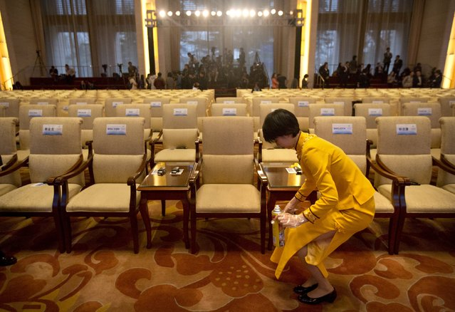An attendant cleans a carpet stain before the opening ceremony of the Asian Infrastructure Investment Bank (AIIB) in Beijing, China January 16, 2016. (Photo by Mark Schiefelbein/Reuters)