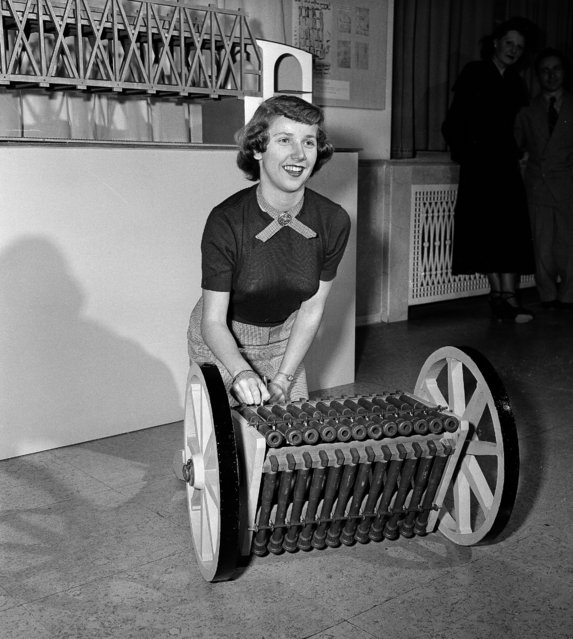 Joan Kramiller of Detroit gets a bang out of the triple-tier machine gun which was designed by Leonardo Da Vinci, Renaissance artist and scientist. This model was constructed by Roberto Guatello and is one of 68 mechanical conceptions based on Da Vinci sketches which were on view at The Edison Museum in Dearborn, Mich., January 19, 1950. The machine gun has twelve guns in each tier. One tier was to be fired while a second was being loaded and the third was cooling. (Photo by Preston Stroup/AP Photo)