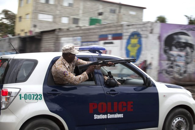 A national police officer fires birdshot at demonstrators during a street protest after it was announced that the runoff Jan. 24, elections had been postponed, in Port-au-Prince, Haiti, Friday, January 22, 2016. The Provisional Electoral Council in Haiti has postponed the election amid escalating protests by the opposition, which claims the first round was marred by fraud in favor of a government-backed candidate. (Photo by Dieu Nalio Chery/AP Photo)