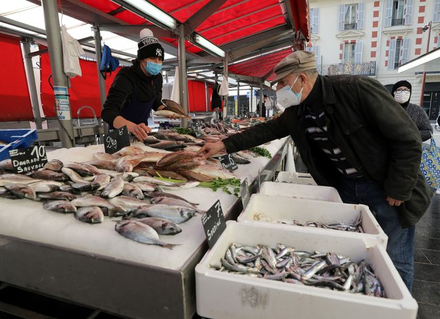 A man, wearing a protective face mask, shops at a fishmonger at a local market in Nice amid the coronavirus disease (COVID-19) outbreak in France, February 18, 2021. (Photo by Eric Gaillard/Reuters)