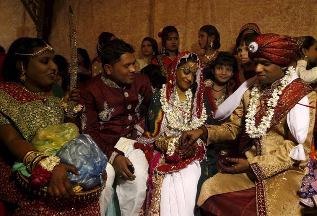 A bride and groom couple go through a ritual during a mass marriage ceremony in Karachi, Pakistan, January 24, 2016. (Photo by Akhtar Soomro/Reuters)