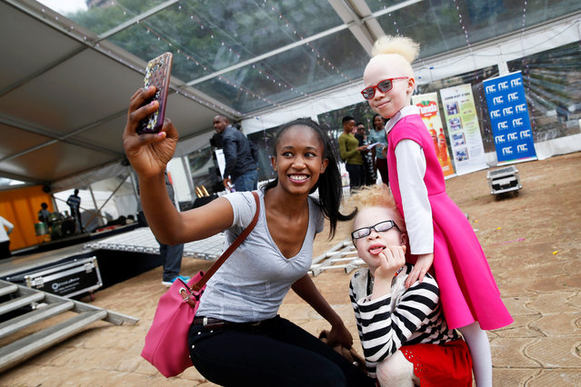 A woman takes a selfie with Shirlyne Wangari and Rebecca Zawadi before the Mr & Miss Albinism Kenya Beauty Pageant 2018 in Nairobi, Kenya, November 30, 2018. (Photo by Baz Ratner/Reuters)