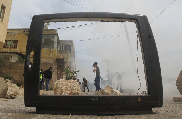 An image shot through the frame of a broken television shows Palestinian protesters during clashes with Israeli security forces after a demonstration against the expropriation of Palestinian land by Israel in the village of Kfar Qaddum, near Nablus in the occupied West Bank, on March 27, 2015. (Photo by Jaafar Ashtiyeh/AFP Photo)