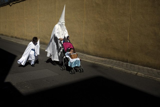 Penitents from the La Paz brotherhood walk to the church to take part in a procession in Seville, Spain, Sunday, March 29, 2015. (Photo by Emilio Morenatti/AP Photo)