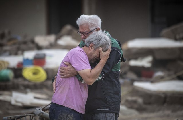 Two brothers weep in each other's arms in front of their parents' house, which was destroyed by the flood in Altenahr, Germany, Monday, July 19, 2021. Numerous houses in the town were completely destroyed or severely damaged, there are numerous fatalities. (Photo by Boris Roessler/dpa via AP Photo)