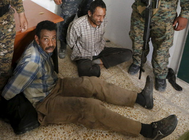 Shi'ite paramilitary fighters and Iraqi security forces arrest Islamic State militants in Tikrit April 1, 2015. (Photo by Thaier Al-Sudani/Reuters)