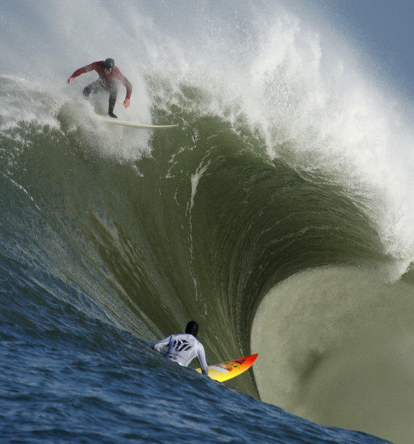 """In this February 13, 2010, file photo, Evan Slater, top, surfs a giant wave over Darryl """"Flea"""" Virostko during the first heat of the Mavericks surf contest in Half Moon Bay, Calif. The world's best big-wave competition, Titans of Mavericks has been set for Friday, February 12, 2016. Mavericks is the world's premiere, high adrenaline, big wave surfing event is a one-day invitation-only surfing competition that is held at the legendary Mavericks surf break located near Half Moon Bay, about 20 miles south of San Francisco. (Photo by Ben Margot/AP Photo)"""