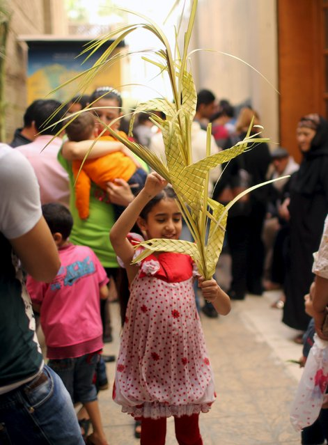 An Egyptian Coptic Christian girl carries a palm decoration during Palm Sunday inside a church in Old Cairo, April 5, 2015. (Photo by Asmaa Waguih/Reuters)